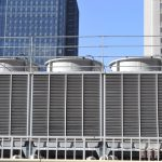HVAC cooling tower heat exchanger on top of a building in front of commercial building stocks